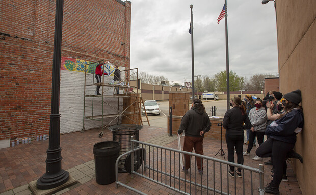 Students watch as a stencil design is finalized in the Havelock Avenue mural.