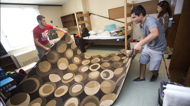 Michelle Huesca of Omaha (right) and Matt Willis of Blair unroll their carpet in their Smith Hall room.