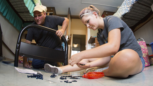 Cassandra Huck of Bayard, and her dad, Randy, work to assemble a futon in her Harper Residence Hall room during move in on Aug. 21.