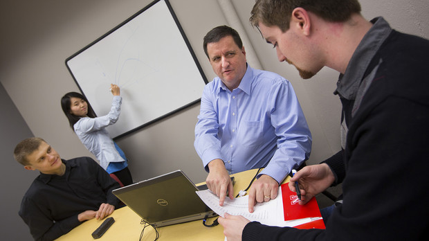 Eric Thompson (second from right), associate professor of economics, works with student research assistants in the College of Business Administration's Bureau of Business Research. The bureau is designed to assist with Nebraska's economic development efforts.