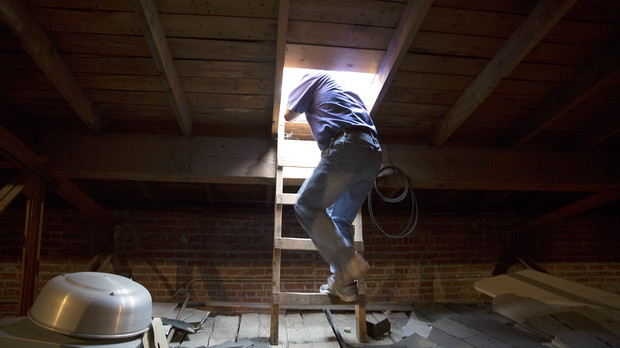 Bryan Ludemann climb through a hatch to assess possible leaks on the roof of Chase Hall on June 11.