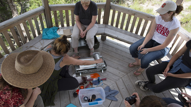 Students create prints of plant material in a gazebo atop a bluff at Cedar Point Biological Station. Kunc provided a backpack printing press that allowed students to generate designs while in the field.