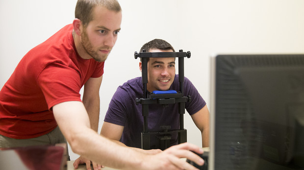Mark Mills (left), professor of political science, sets up an eye track computer as part of a study.