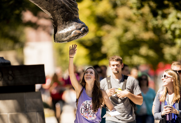A Nebraska student reaches up to give the Archie sculpture a high-five. Campus legend claims that a high-five from the mammoth brings good luck.