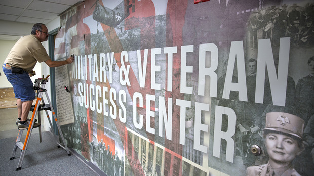 Dave Godin of Renze Display installs a wall mural outside of UNL's new Military and Veteran Success Center in the Nebraska Union. The office, which will offer support to student veterans, members of the military and their dependents, opens Sept. 11.