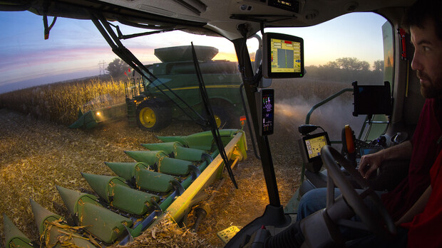 A farmer harvests corn while watching data regarding the harvest quality on a computer in his combine.