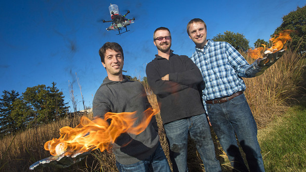 Sebastian Elbaum (from left), Dirac Twidwell and Carrick Detweiler have developed a patent for setting range fires with small drones. The drone injects a liquid into plastic spheres to start a delayed fiery process that allows the balls to fall to the ground before igniting. Elbaum and Detweiler are holding flaming tennis balls similar to those carried by the drones.