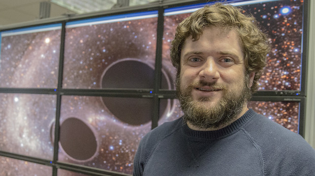 Brian Bockelman, research assistant professor of computer science and engineering, stands in front of a graphic that shows two black holes merging. Bockelman and colleagues assisted with the porting of code from LIGO's data facilities.