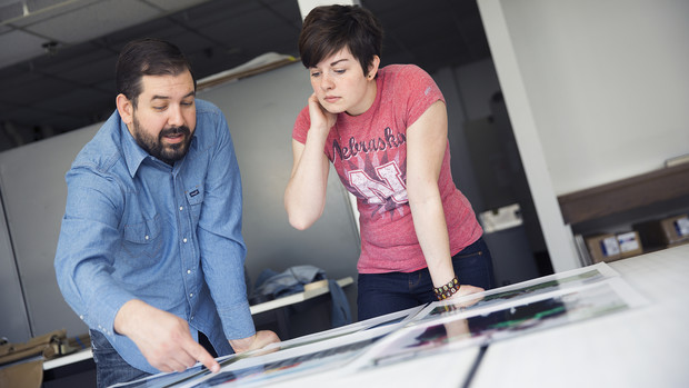 Walker Pickering (left) discusses print quality with his UCARE student Shalbey Workman. Pickering is a photography professor who has created a series of behind-the-scenes photos of marching bands and drum corps from high school to college.