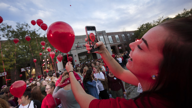 Kylie Gunderson photographs her balloon before the release during the 2016 homecoming pep rally.