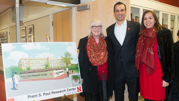 Members of Prem S. Paul's family stand next to a architectural drawing of new signage that will be installed on the south side of the recently renamed Prem S. Paul Research Center at Whittier School. Pictured (from left) is Prem's widow, Missi Paul; son Ryan Paul; and daughter Neena Paul.