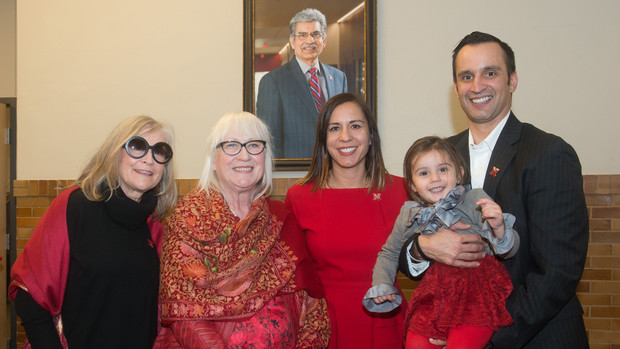 Prem S. Paul's family stands in front of a portrait of Nebraska's longtime vice chancellor for research and economic development. Pictured (from left) is Kiki Fink, Missi Paul, Neena Paul and Ryan Paul, who is holding granddaughter Ashland. Fink is Missi Paul's sister.