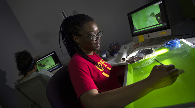 "Imani Brown, a sophomore art student, paints over live-action scenes with an animation technique called rotoscoping. Brown, whose career goal is to create animated cartoons, is part of a team at Nebraska that is creating an animated film depicting the life of Ann ""Anna"" Williams, an enslaved woman who jumped out of a third-story window in Washington D.C. in 1815  after she had been sold into the cotton industry.  Another student animator, Thalia Rodgers, a senior art student, works on another part of the scene in the background."