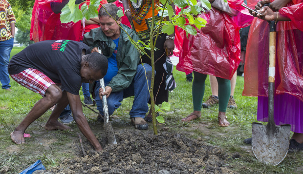 Vincent Kumwenda (left), a Mandela Washington Fellow in summer 2017, places a time capsule next to the roots of a London Planetree as Nebraska's Laurence Ballard uses a shovel to hold back soil. The event was part of a Mandela Day observance during the fellows' 2017 visit to Nebraska.