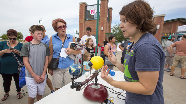 Vida Nixon, a sophomore physics and astronomy student, explains a solar eclipse during the science expo outside Hawks Field. The expo featured 15 booths with students, faculty and staff discussing science and research topics.