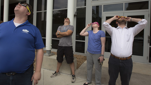 NIMBUS Lab members (from left) Andrew Rasmussen, Adam Plowcha and Brittany Duncan, and Jarrett Ramsay, a Nebraska alumnus, view the eclipse outside the Schorr Center.