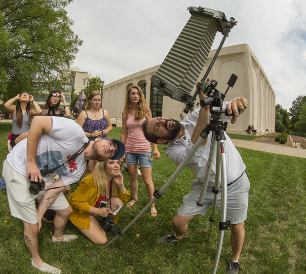 Walker Pickering (right) and introductory to photography students look at the eclipse through a view camera in the Sheldon Sculpture Garden.
