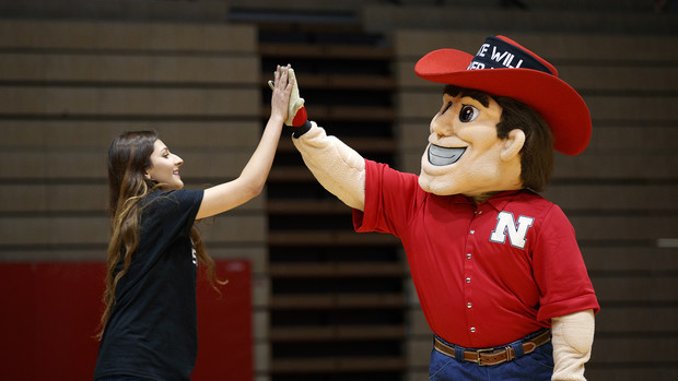 Ayat Aribi, external vice president of ASUN, gets a high five from Herbie Husker as she approaches the stage to talk during the Feb. 14 rally.