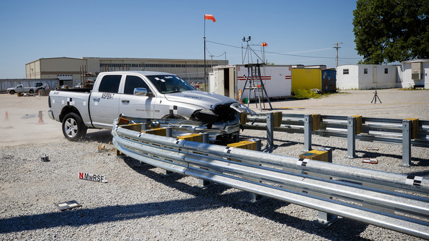 A truck crashes into a bull-nose barrier being tested for use in medians to protect cars from overpass columns. The front wood pylons are designed to shear off easily along with several metal ones. The shearing allows the energy of the crash to be transferred into the ground. Cables in the guard rails are designed to keep the car or truck captive and not let it deflect back into traffic.