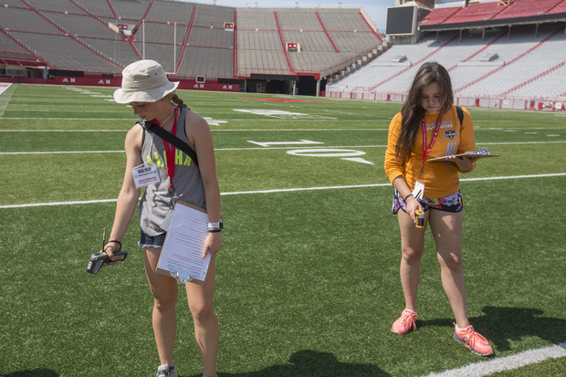 Weather campers Grace Schlepping (left) and Awinita Bunner take temperature measurements on the turf of Memorial Stadium June 14.