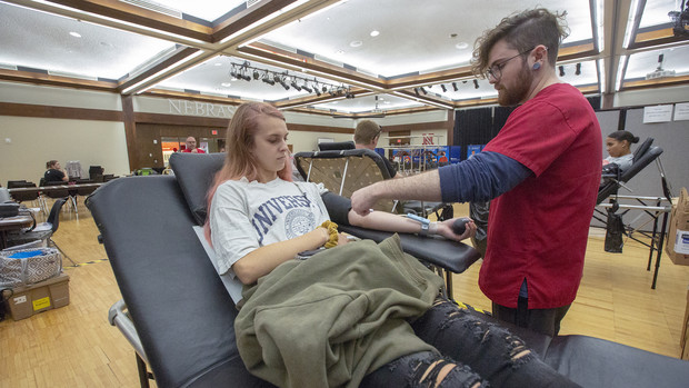Nebraska's Anna Drelicharz watches as Logan Grimm of the American Red Cross adjusts a needle during the homecoming blood drive on Sept. 25. The donation was Drelicharz's first.