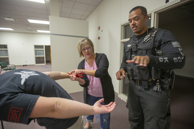 K-9 Officer Russell Johnson Jr. (right) shows Julie Thomsen how to apply handcuffs during the second week of the University Police Department's Citizens' Police Academy. The six-week program is designed to educate members of the campus community about the University Police Department.