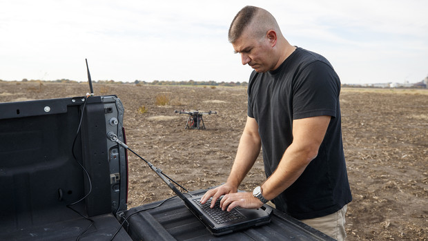 Adam Plowcha checks the status of a drone during a field test. After earning a doctorate, Plowcha hopes to continue working with drones either in academia or industry.