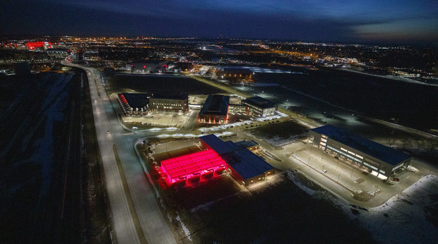 Greenhouses at Nebraska Innovation Campus glow red with Memorial Stadium and City Campus in the background.