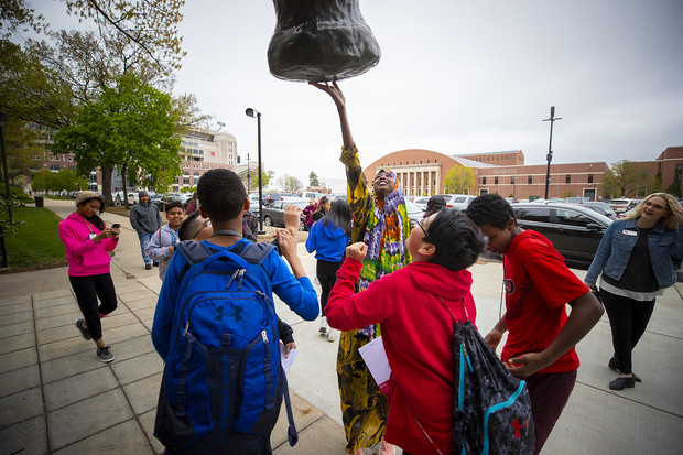Lexington middle school students and chaperones reach to touch the good luck foot of the mammoth sculpture outside of Morrill Hall during a campus tour on May 1. Along with tours, Nebraska's middle school-related programs include Next Chapter at Nebraska, Big Red Stars and Middle School College Access Days.