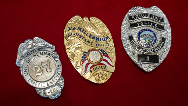 Badges worn by University Police at Nebraska have changed many times through the years. Badges shown (from left) are: a design worn from the 1930s to late 1960s; the millennium badge worn in 2000; and the current regulation design, featuring the Nebraska state seal. These three badges were worn by Bill Manning, who previously served with the University Police and is now with Parking and Transit Services.
