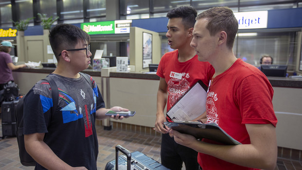 Simon Chen (left) talks with two members of the Nebraska welcome team after his arrival in Lincoln.