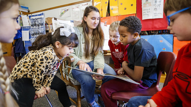 Megan Groth, a sophomore speech-language pathology major, reads to first-grade students at Saratoga Elementary school as part of the America Reads/America Counts project.