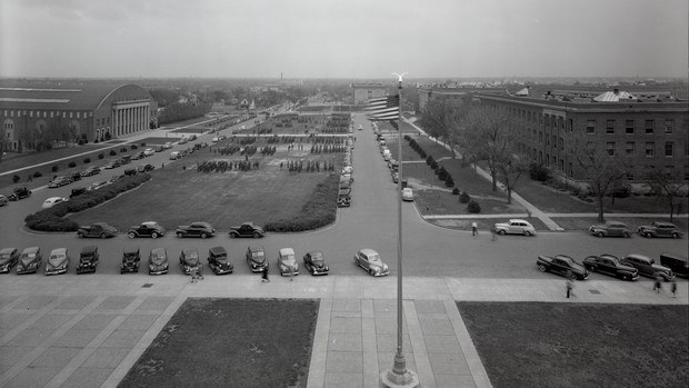 Nebraska ROTC students march on the green space east of Memorial Stadium in for a Chancellor's Review in April 1942. Taken from atop Memorial Stadium, this image includes the Coliseum (left), Bessey Hall (right, bottom) and Morrill Hall (right, top)