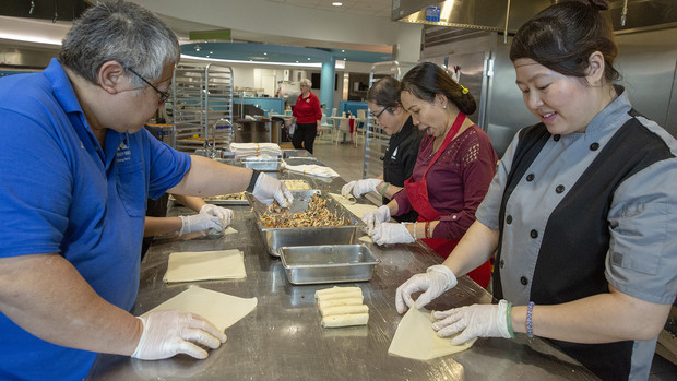 "Team members work through the final pan of homemade egg roll filling in the World's Fare station in the Cather Dining Center. Pictured at the table (from left) is Tri Tu, Kim Nguyen (hidden by Tu), Amy Tran, Ha Vu and Thom ""Emily"" Tran."