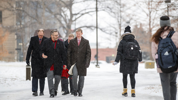 Ronnie Green and Ted Carter walk across City Campus as snow fell on Jan. 17. Carter heralded his enthusiasm for the weather and tour in a tweet.