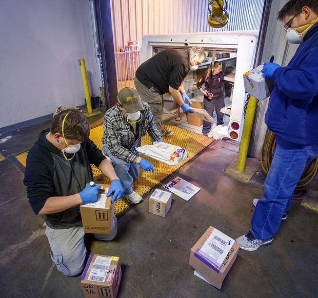 University employees sort packages after a morning delivery at the Facilities Management Shops on N. 22nd St. The facility has been set up to serve as a central distribution point for the majority of packages delivered to campus during the COVID-19 pandemic.