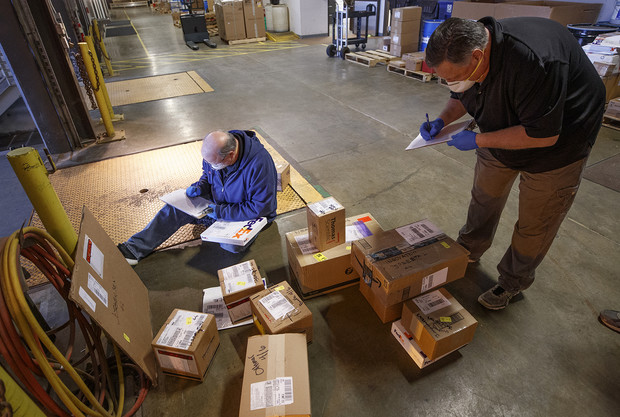 Pat Huberty (from left) and Ed Kerney check in and sort packages following a FedEx delivery. Package delivery has been consolidated at the Facilities Management Shops on north 22nd St. There, the packages are sorted, logged in and the recipients notified to pick up the package or have it stored until they return.