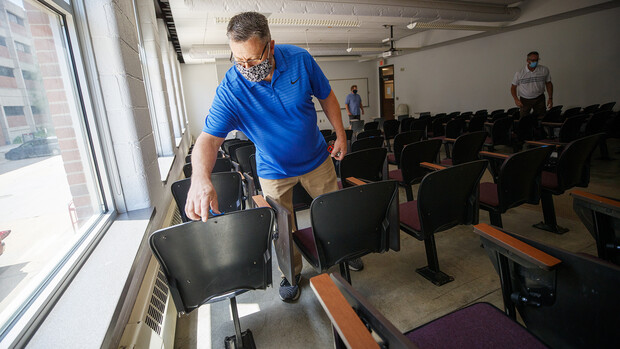 Shawn Languis places tape on the back of a chair that will be unavailable due to six-foot social distancing guidelines. The group is physically measuring every classroom on campus to see if computer-aided predictions are correct.