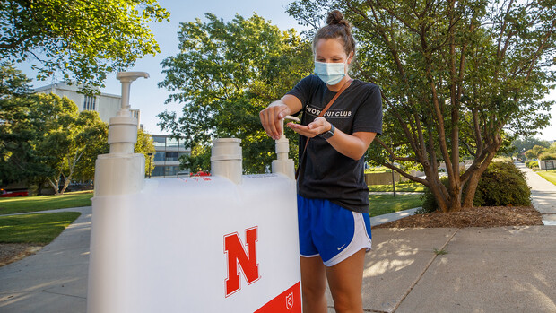 Maggie Ferguson, a May 2020 College of Business graduate, tests a hand-sanitizer station outside of Westbrook Music Building on July 28. The station is one of the more than 1,500 being distributed around the university.