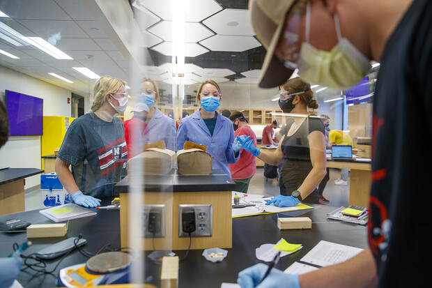 Sarah Brady, a chemistry lab teaching assistant (center, in blue), answers questions during a lesson in Hamilton Hall. Acrylic dividers are being used in the space to increase capacity of the lab space.