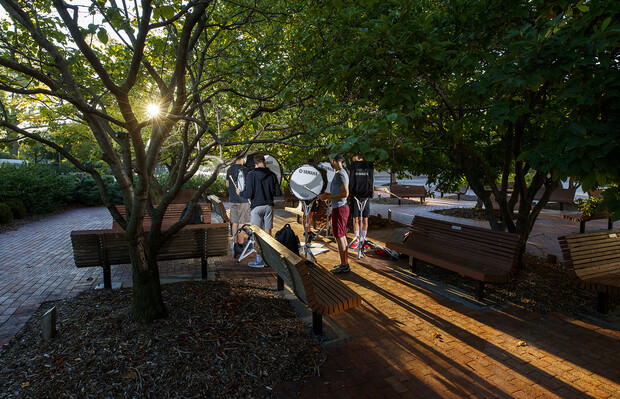The bass line offers up a sunrise serenade under the trees outside the Lied Center for Performing Arts.