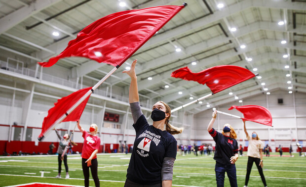 Michaela Smith and other members of the Cornhusker Marching Band color guard take their flags out for an early morning spit during practice in Cook Pavilion on Sept. 10.