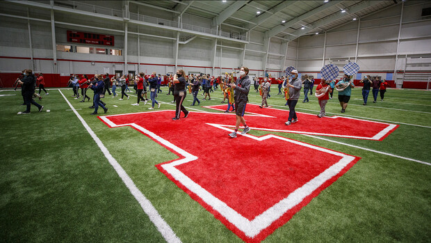 A third of the Cornhusker Marching Band plays during an early-morning practice in Cook Pavilion. As part of its COVID-19 health protocols, the band limits the number of students participating in practice to a maximum of two-thirds of total members. They have also doubled the distance between each musician and are either wearing masks or have the bells of wind instruments covered with cloth.