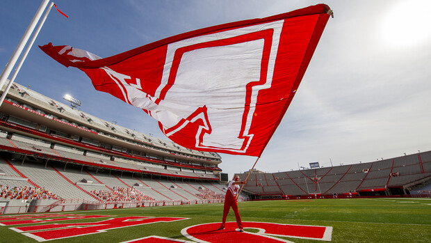 "A member of the Husker cheer squad flies an ""N"" flag in the end zone during a taping event on Oct. 18. HuskerVision has recorded a number of game day experiences and will offer them through Husker football livestream."