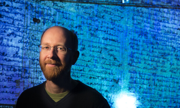 Adrian Wisnicki, assistant professor of English, stands in front of a projected image of David Livingstone's 1871 diaries.