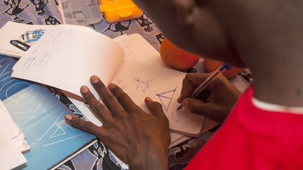 A student sketches possible changes to his teams robot during Sidy Ndao's robotics camp in Dakar, Sengal.