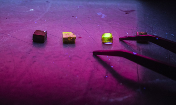 Three crystals of methylammonium lead tribromide are illuminated by ultraviolet light. High-quality crystals suitable for X-ray detection glow green when struck by an ultraviolet laser, as illustrated by the crystal at far right.
