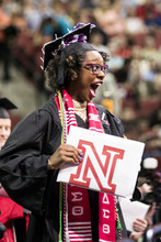 Mecca Slaughter, who earned a bachelor of journalism, celebrates as she walks off stage during the undergraduate commencement ceremony.
