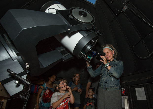 """Visitors look through a telescope at the UNL Student Observatory as part of """"Archie's Late Night Party"""" in 2015."""