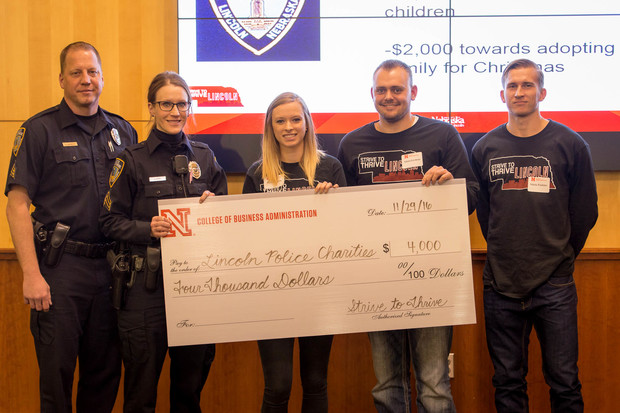 Leading People and Project Management class members present a $4,000 check to the Lincoln Police Department. Pictured (from left) are Officers Chad Barrett and Shannon Karl and students Paxton Barta, Adam Greitens and Nikita Pankins.